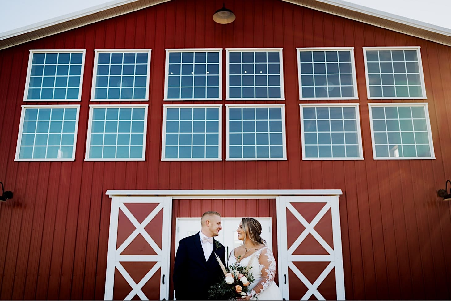 red acre barn with bride and groom